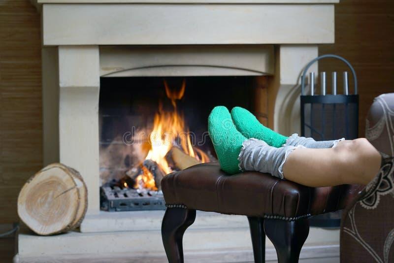 Θηλυκά πόδια στις κάλτσες κοντά στην εστία στοκ εικόνες
