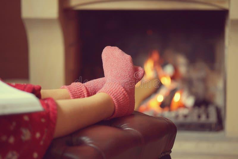 Θηλυκά πόδια στις κάλτσες κοντά στην εστία στοκ εικόνα με δικαίωμα ελεύθερης χρήσης