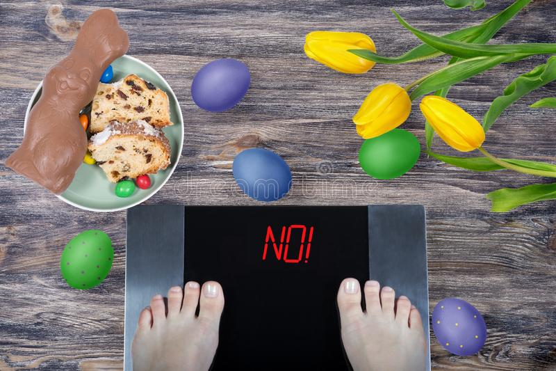 Θηλυκά πόδια στις ψηφιακές κλίμακες με το σημάδι αριθ.! από το κέικ Πάσχας τροφίμων Πάσχας, το λαγουδάκι Πάσχας σοκολάτας, χρωμάτ στοκ φωτογραφίες με δικαίωμα ελεύθερης χρήσης
