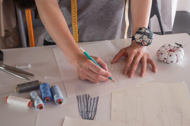 Θηλυκά σκίτσα σχεδίων σχεδιαστών μόδας για τα ενδύματα στο ατελιέ στοκ εικόνα με δικαίωμα ελεύθερης χρήσης