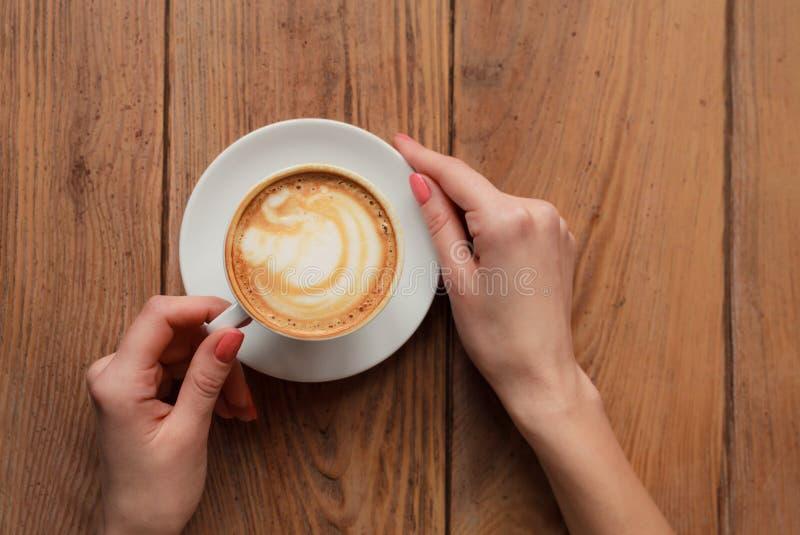 Θηλυκά χέρια κινηματογραφήσεων σε πρώτο πλάνο που κρατούν το φλυτζάνι με το cappuccino καφέ με τον αφρό με το συμπαθητικό σχέδιο  στοκ φωτογραφία με δικαίωμα ελεύθερης χρήσης