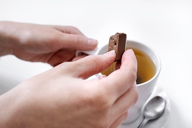 Θηλυκά χέρια με μια σοκολάτα και ένα φλυτζάνι του τσαγιού στοκ φωτογραφίες