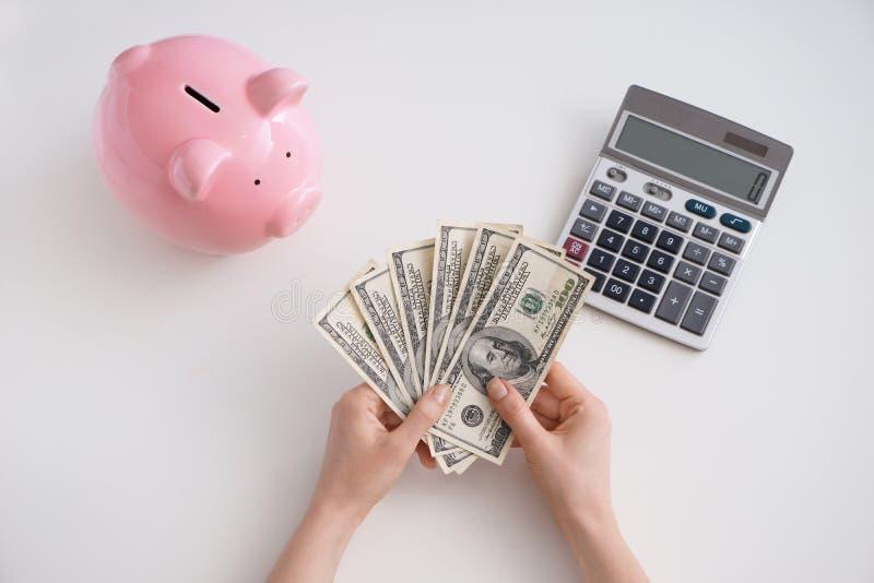 Θηλυκά χέρια με τα δολάρια, τη piggy τράπεζα και τον υπολογιστή στο άσπρο υπόβαθρο, τοπ άποψη στοκ εικόνες με δικαίωμα ελεύθερης χρήσης