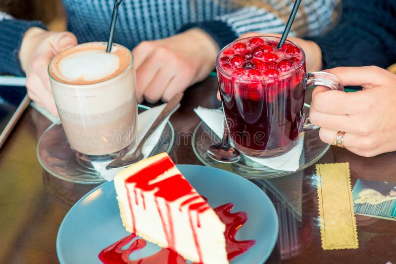 Θηλυκά χέρια με τα ζεστά ποτά και το γλυκό επιδόρπιο στοκ φωτογραφία με δικαίωμα ελεύθερης χρήσης