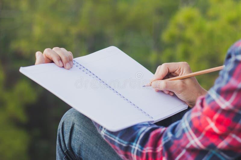 Θηλυκά χέρια με το μολύβι που γράφει στο σημειωματάριο στοκ εικόνα