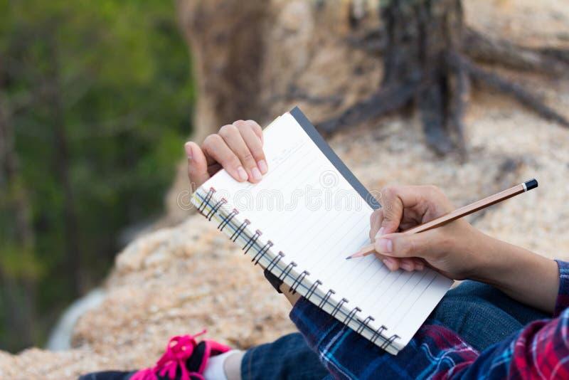 Θηλυκά χέρια με το μολύβι που γράφει στο σημειωματάριο στοκ φωτογραφία με δικαίωμα ελεύθερης χρήσης