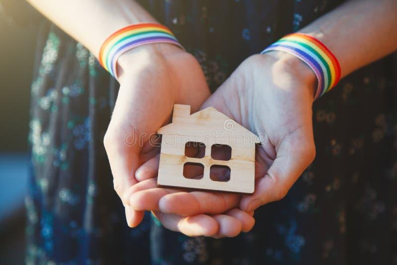Θηλυκά χέρια με το ξύλινο σπίτι τεχνών εκμετάλλευσης κορδελλών ουράνιων τόξων LGBT wristbands στοκ φωτογραφίες με δικαίωμα ελεύθερης χρήσης