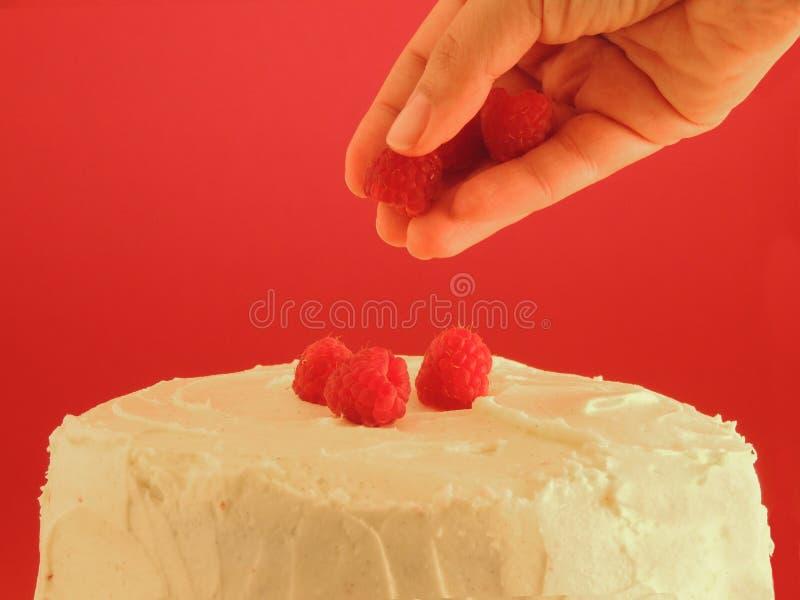 Θηλυκά χέρια που διακοσμούν το άσπρο κέικ σοκολάτας στοκ φωτογραφία