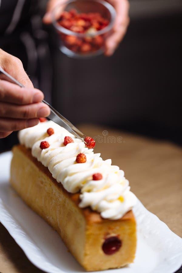 Θηλυκά χέρια που διακοσμούν το κέικ στοκ εικόνα