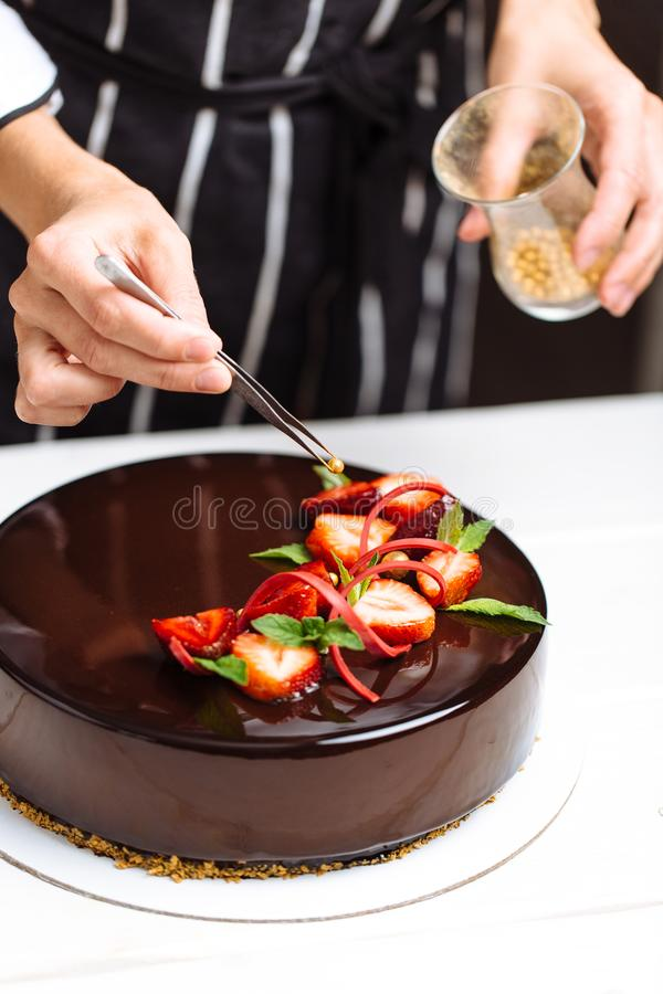 Θηλυκά χέρια που διακοσμούν το κέικ στοκ φωτογραφίες