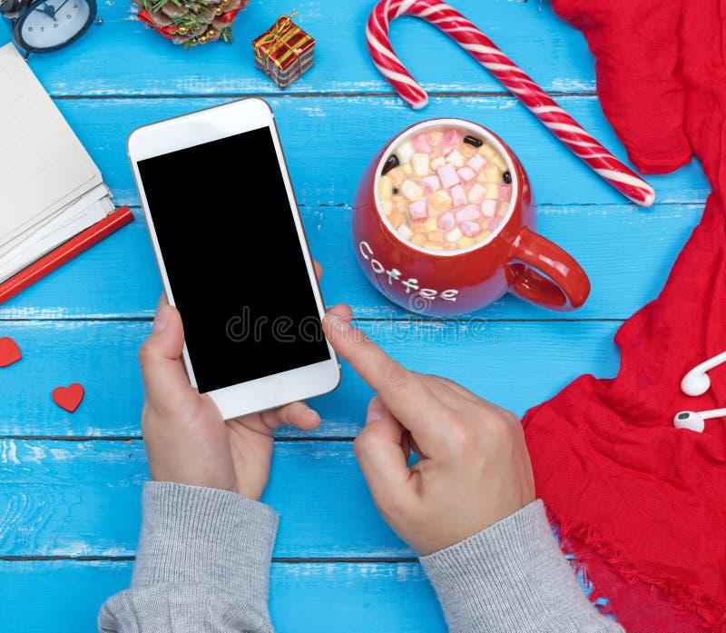 Θηλυκά χέρια που κρατούν το άσπρο έξυπνο τηλέφωνο με την κενή μαύρη οθόνη στοκ εικόνα με δικαίωμα ελεύθερης χρήσης