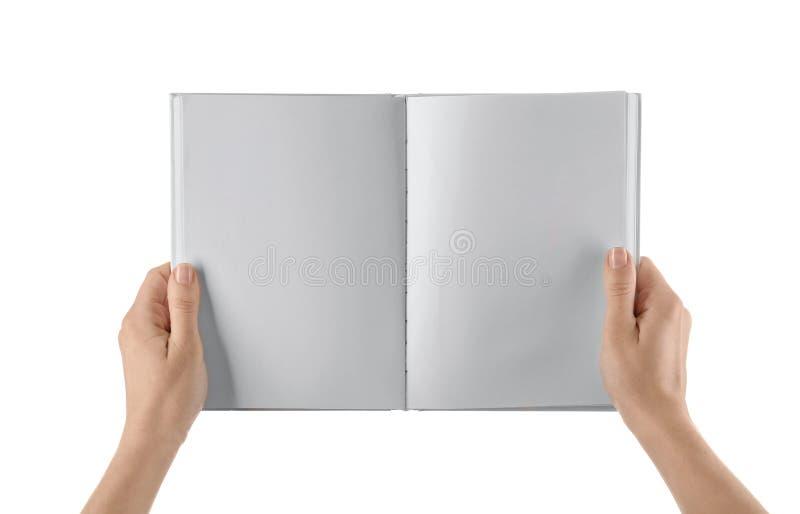 Θηλυκά χέρια που κρατούν το βιβλίο με τις κενές σελίδες στο άσπρο υπόβαθρο στοκ φωτογραφία