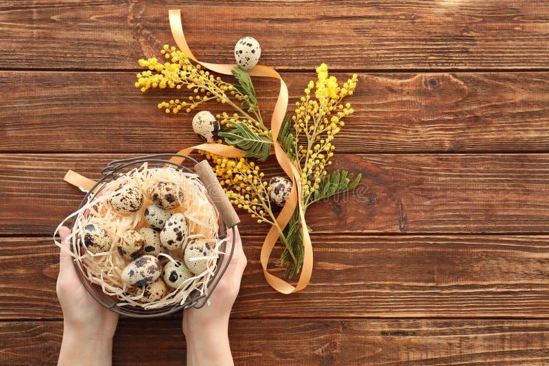 Θηλυκά χέρια που κρατούν το καλάθι Πάσχας γεμισμένο με τα αυγά ορτυκιών, στο ξύλινο υπόβαθρο στοκ εικόνες