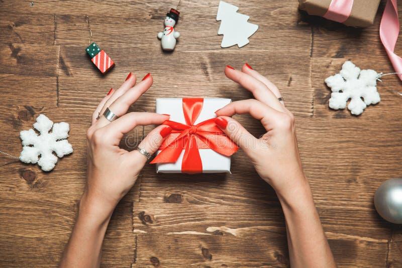 Θηλυκά χέρια που κρατούν το κιβώτιο δώρων Χριστουγέννων στον ξύλινο πίνακα στοκ φωτογραφία με δικαίωμα ελεύθερης χρήσης