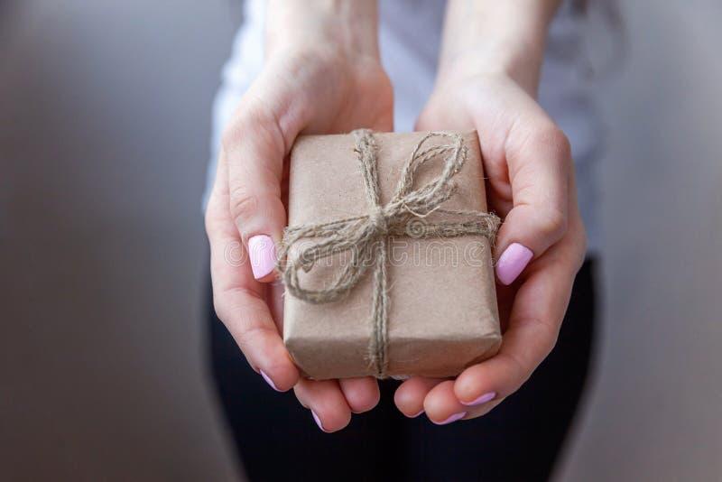 Θηλυκά χέρια που κρατούν το μικρό κιβώτιο δώρων στοκ εικόνες με δικαίωμα ελεύθερης χρήσης