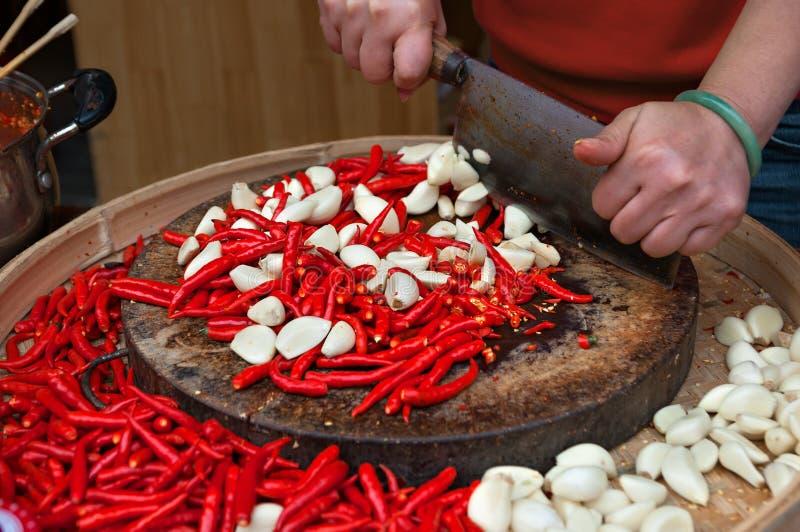 Θηλυκά χέρια που κόβουν τα κόκκινα πιπέρια και το σκόρδο τσίλι στοκ φωτογραφία με δικαίωμα ελεύθερης χρήσης