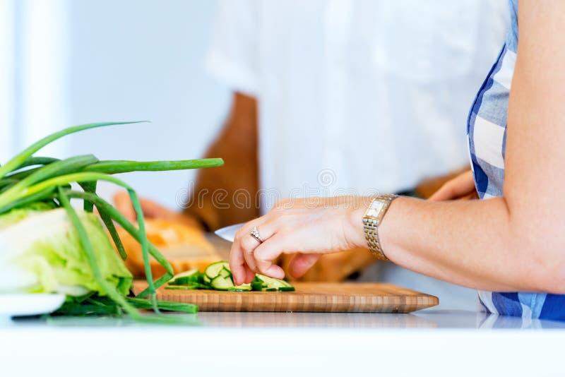 Θηλυκά χέρια που κόβουν το ψωμί στοκ εικόνα