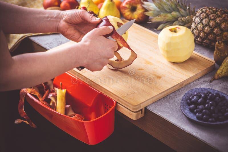 Θηλυκά χέρια που ξεφλουδίζουν τη φρέσκια οργανική Apple με το μικρό μαχαίρι στοκ φωτογραφία