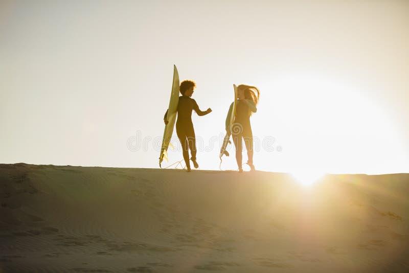 Θηλυκά surfers στην παραλία στοκ φωτογραφία με δικαίωμα ελεύθερης χρήσης