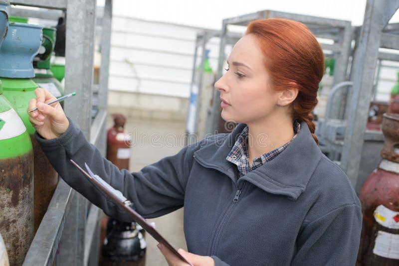 Θηλυκές δεξαμενές αερίου επιθεώρησης εργαζομένων στοκ εικόνα