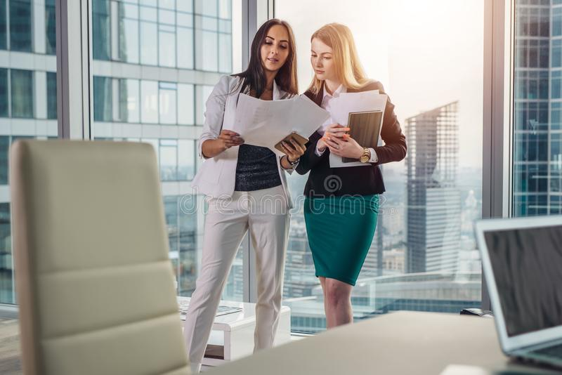 Θηλυκές επιχειρηματίες που φορούν την επίσημη εξάρτηση που συζητά τα έγγραφα που στέκονται στο διάδρομο γραφείων στοκ φωτογραφίες με δικαίωμα ελεύθερης χρήσης