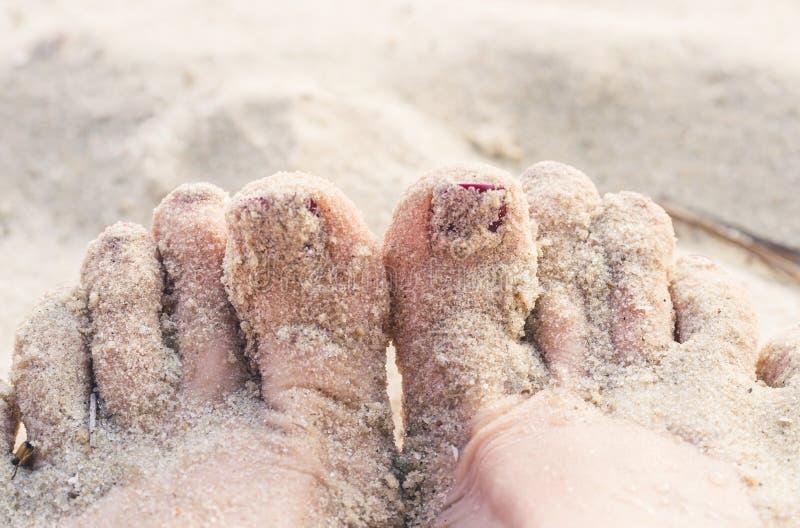 Θηλυκές πόδια και άμμος μιας θερινής παραλίας στοκ εικόνες