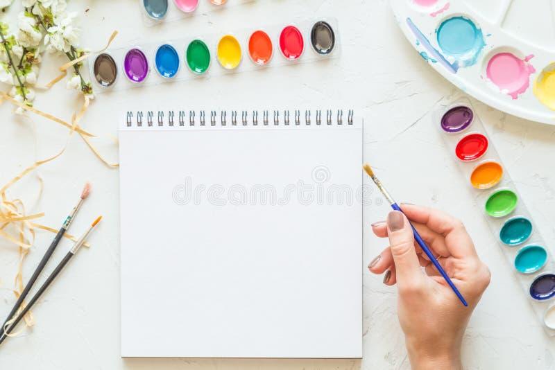 Θηλυκή βούρτσα εκμετάλλευσης χεριών, να βρεθεί φωλιών watercolor και άσπρο σημειωματάριο Επίπεδος βάλτε, τοπ άποψη τοποθετήστε το στοκ εικόνα με δικαίωμα ελεύθερης χρήσης