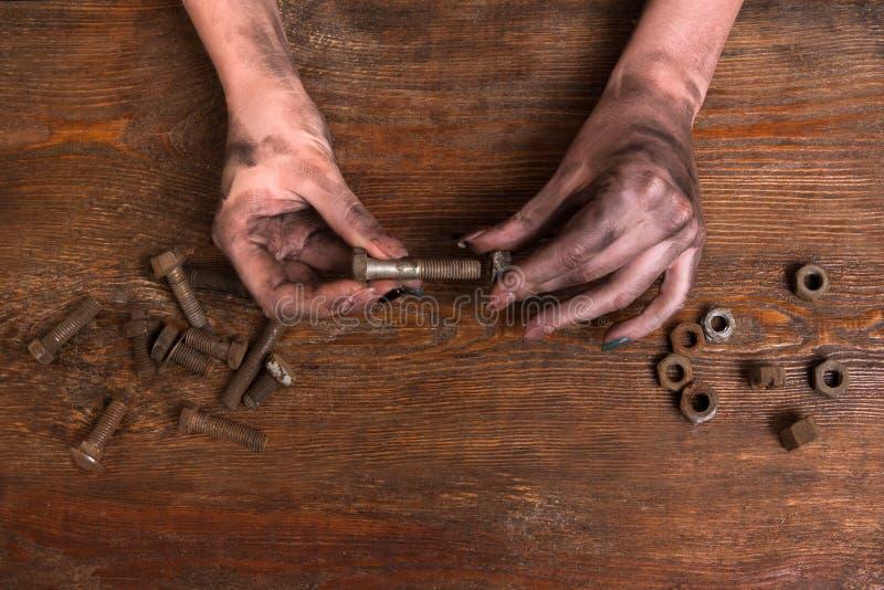 Θηλυκή βρώμικη σύγχρονη εργασία μπουλονιών καρυδιών βιδών χεριών στοκ εικόνες με δικαίωμα ελεύθερης χρήσης