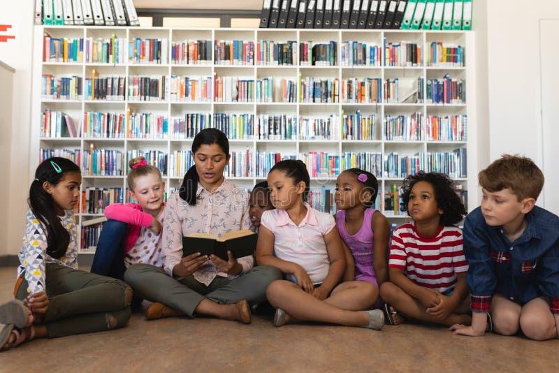Θηλυκή διδασκαλία δασκάλων schoolkids και συνεδρίαση στο πάτωμα της σχολικής βιβλιοθήκης στοκ εικόνες