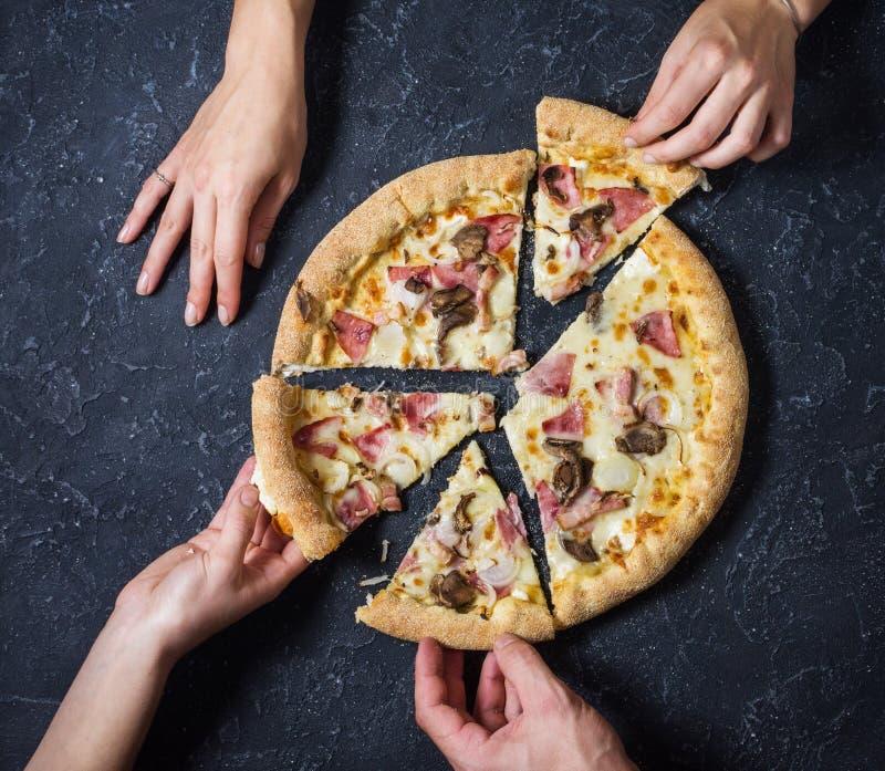 Θηλυκή και αρσενική πίτσα Carbonara περικοπών χεριών στο μαύρο υπόβαθρο πετρών Ιταλική πίτσα Carbonara με το μπέϊκον, μανιτάρια κ στοκ φωτογραφίες