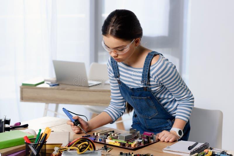 θηλυκή μητρική κάρτα υπολογιστών εφήβων συγκολλώντας με το συγκολλώντας σίδηρο στοκ φωτογραφίες με δικαίωμα ελεύθερης χρήσης