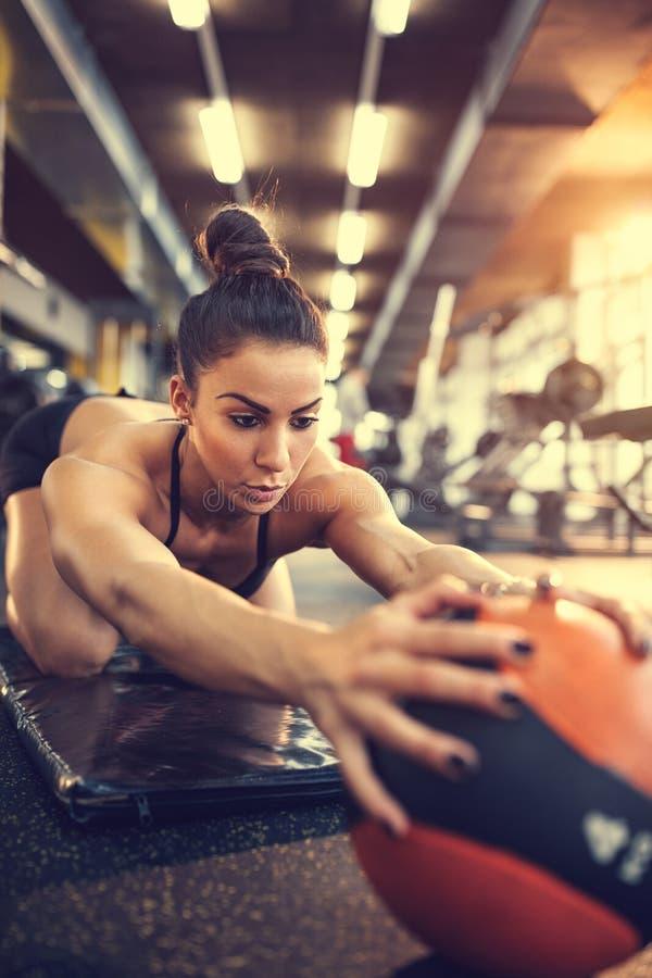Θηλυκή να κάνει άσκηση με τη σφαίρα στο κέντρο ικανότητας στοκ εικόνα