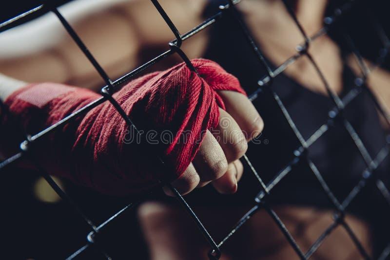 Θηλυκή πυγμή στους επιδέσμους για τον εγκιβωτισμό των καγκέλων δαχτυλιδιών αρπαγών Έννοια της δύναμης, φεμινισμός στοκ εικόνες