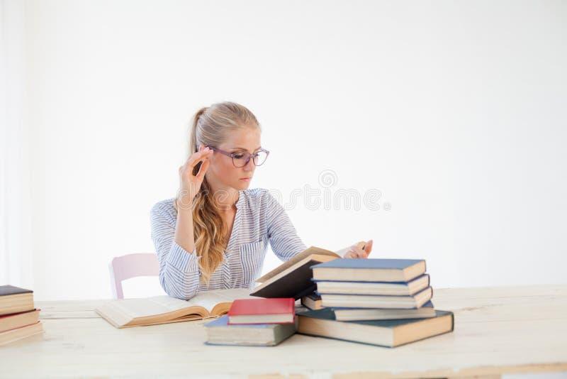 Θηλυκή συνεδρίαση δασκάλων σε έναν πίνακα του γραφείου πολλών βιβλίων στοκ εικόνα