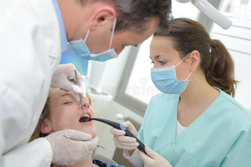 Θηλυκή συνεργασία οδοντιάτρων με τον ασθενή στοκ φωτογραφίες