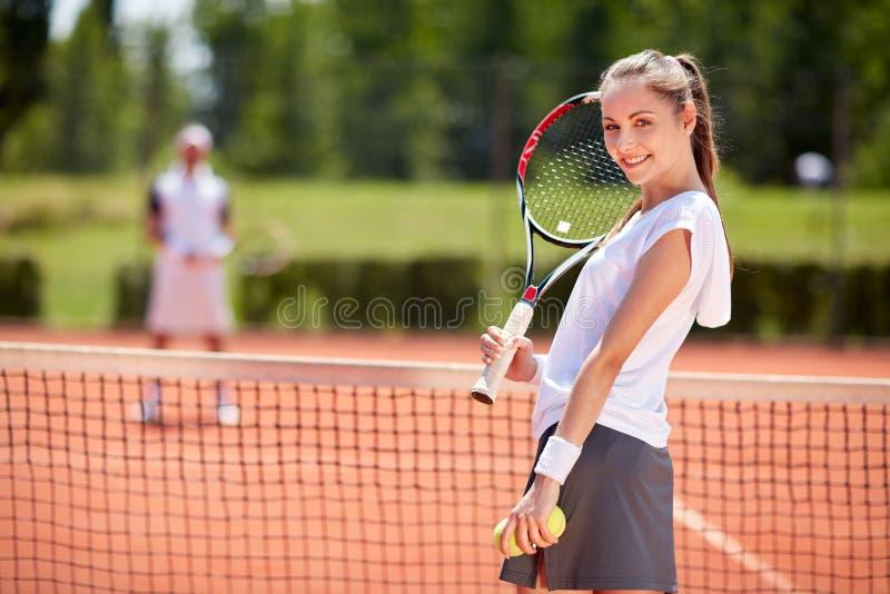 Θηλυκή τοποθέτηση τενιστών στο γήπεδο αντισφαίρισης στοκ εικόνα με δικαίωμα ελεύθερης χρήσης