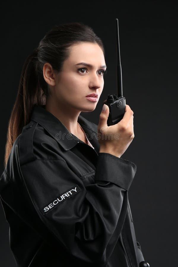 Θηλυκή φρουρά ασφάλειας που χρησιμοποιεί τη φορητή ραδιο συσκευή αποστολής σημάτων στοκ φωτογραφία