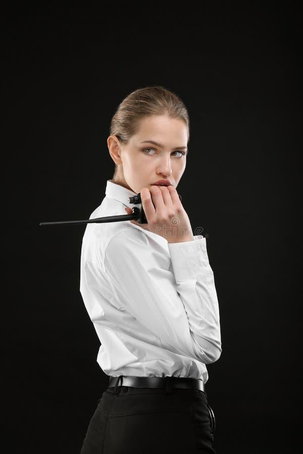 Θηλυκή φρουρά ασφάλειας που χρησιμοποιεί τη φορητή ραδιο συσκευή αποστολής σημάτων στοκ φωτογραφίες