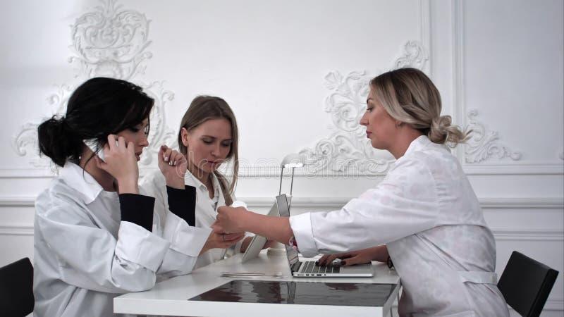Θηλυκοί γιατροί που εργάζονται με τα έγγραφα στο ιατρικό γραφείο στοκ φωτογραφία με δικαίωμα ελεύθερης χρήσης