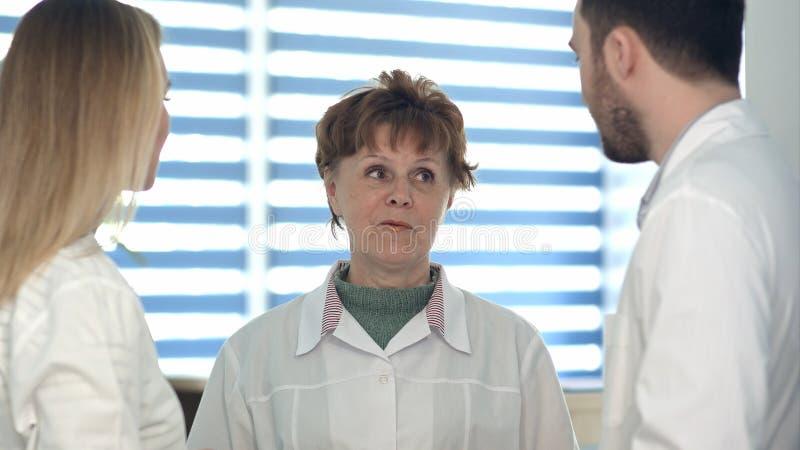 Θηλυκοί και αρσενικοί γιατροί που μιλούν σε μια παλαιότερη νοσοκόμα στοκ φωτογραφία με δικαίωμα ελεύθερης χρήσης