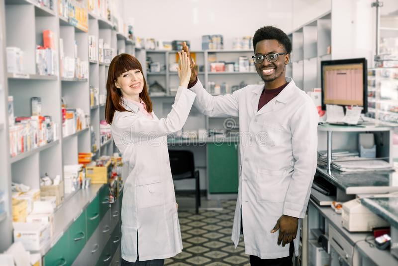 Θηλυκοί και αρσενικοί φαρμακοποιοί στο φαρμακείο Αφρικανικός άνδρας και καυκάσια γυναίκα που δίνουν πέντε, εργαζόμενος στο σύγχρο στοκ φωτογραφία με δικαίωμα ελεύθερης χρήσης