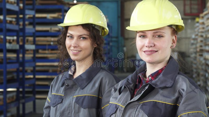 Θηλυκοί μηχανικοί που φορούν προστατευτικά hardhats που χαμογελούν στη κάμερα στοκ φωτογραφία