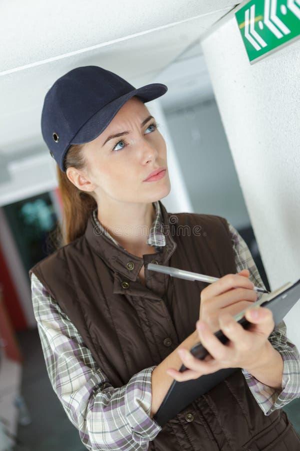 Θηλυκοί μηχανικός και τεχνικοί που ελέγχουν τον κατάλογο στην περιοχή αποκομμάτων στοκ φωτογραφίες