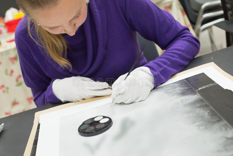 Θηλυκοί ξανθοί καλλιτέχνες φωτογραφιών retoucher που εργάζονται στο αναλογικά σιτάρι και blemishes καθορισμού τυπωμένων υλών Καλώ στοκ φωτογραφία με δικαίωμα ελεύθερης χρήσης