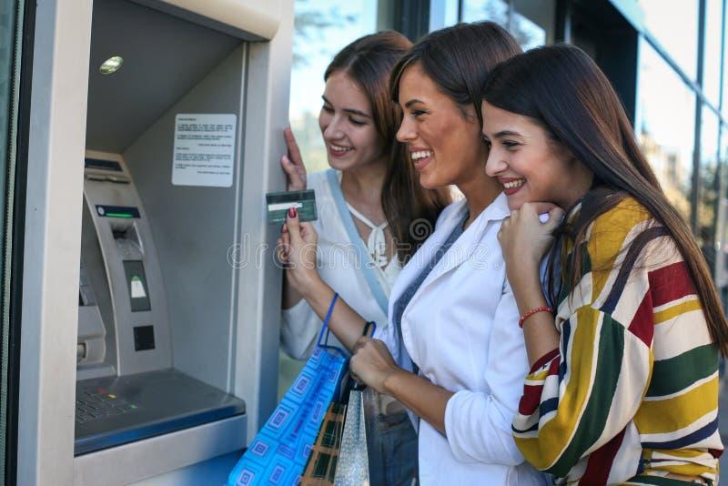 Θηλυκοί φίλοι που χρησιμοποιούν τη μηχανή του ATM στοκ φωτογραφία με δικαίωμα ελεύθερης χρήσης