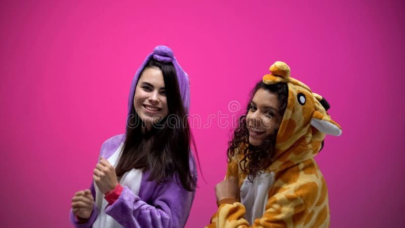 Θηλυκοί φίλοι στις πυτζάμες μονοκέρων και giraffe που χορεύουν, κόμμα καρναβαλιού, χρόνος διασκέδασης στοκ φωτογραφία με δικαίωμα ελεύθερης χρήσης