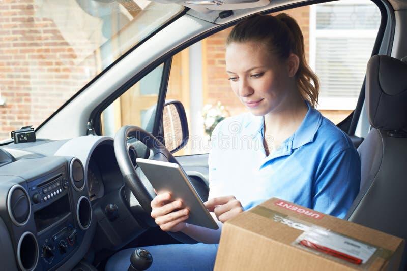 Θηλυκός αγγελιαφόρος Van With στη Digital ταμπλέτα που παραδίδει τη συσκευασία στοκ φωτογραφία