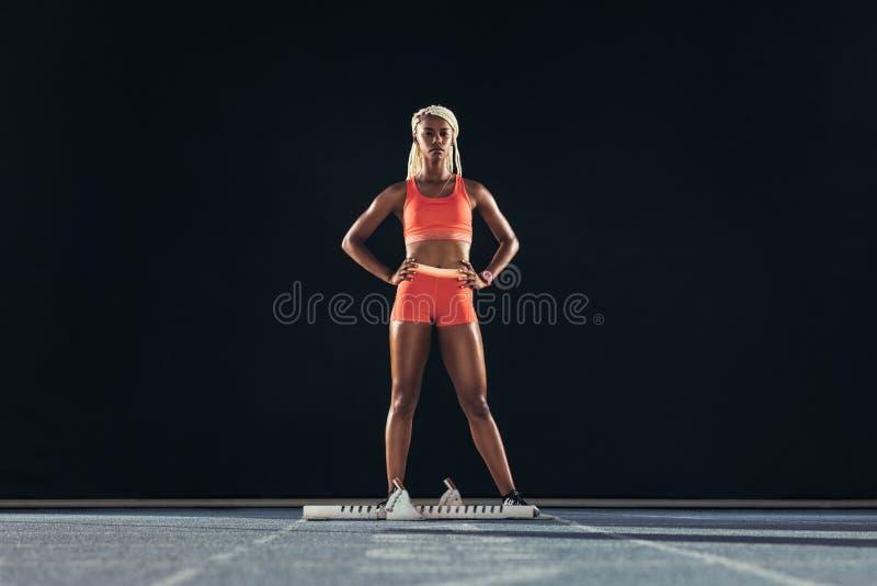 Θηλυκός αθλητής που στέκεται σε μια τρέχοντας διαδρομή στοκ φωτογραφία με δικαίωμα ελεύθερης χρήσης