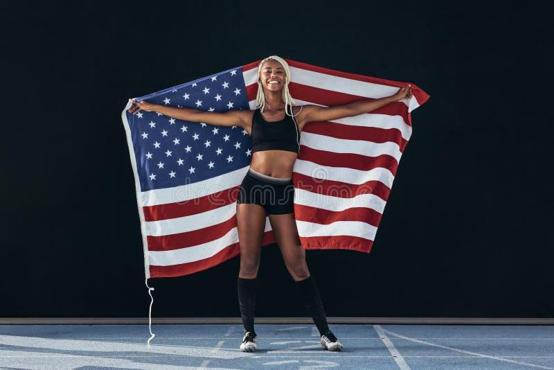 Θηλυκός αθλητής που στέκεται στο τρέξιμο της αμερικανικής σημαίας εκμετάλλευσης διαδρομής στοκ φωτογραφίες με δικαίωμα ελεύθερης χρήσης