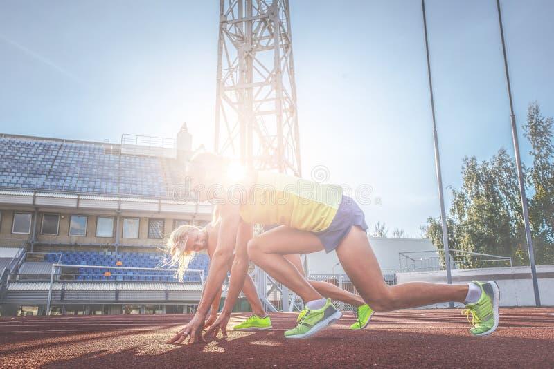 Θηλυκός αθλητής sprinter δύο που παίρνει έτοιμος να αρχίσει έναν αγώνα σε μια κόκκινη τρέχοντας διαδρομή στο στάδιο αθλητισμού στοκ φωτογραφία